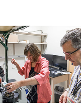 Emily Gibson and Diego Restrepo examined the miniature microscope they developed with two professors from CU Boulder. The team won a $2 million NIH Brain Initiative grant to refine and expand the use of the instrument.