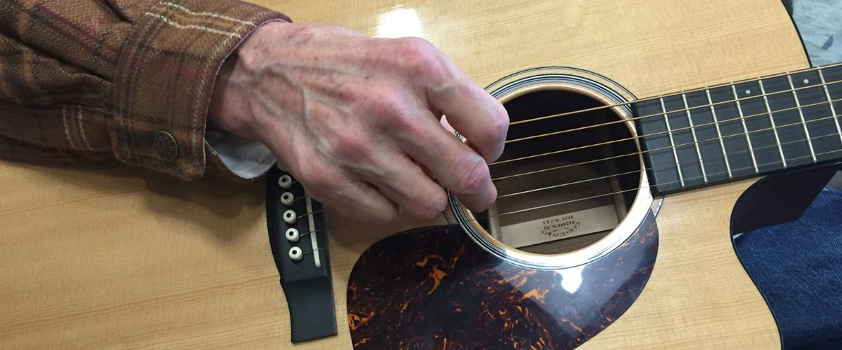 A patient in the Natalie Kutner Palliative Care Creative Arts Therapy Program plays the guitar